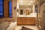 Master bathroom with a double vanity, walk-in shower, and soaking tub